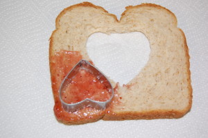 Spread a little jelly on the corner of your bread slice and use a smaller heart cutter to cut it out.