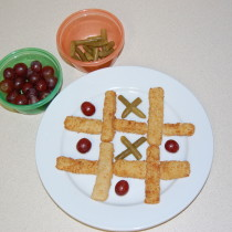 Tic Tac Toe with fish sticks, green beans and grapes.
